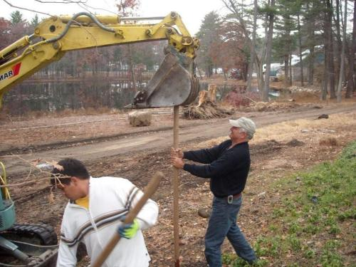 Paul Cavicchio holding a guy stake for the machine to push into the ground